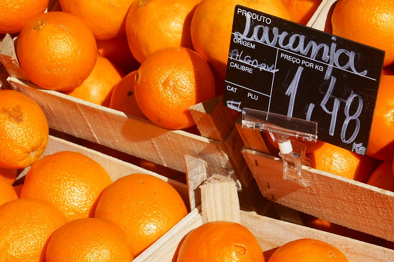 A sign at a fruit market in Lisbon for 'laranja' specifies the fruit's origin as the Algarve.