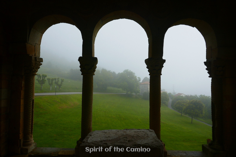 Looking through the arches of Santa María del Naranco at the greenery and fog of Asturias.