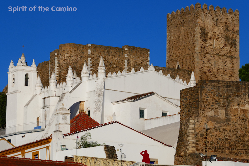 Mértola's skyline: The whitewashed church built on the foundations of a mosque, with a Christian castle in the background.