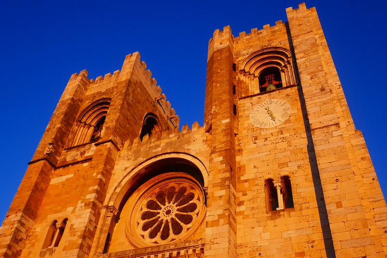 Late afternoon light hits the façade of Lisbon's 12th-century cathedral and gives it an orange hue.
